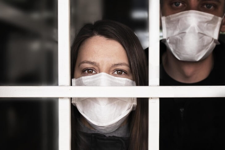 Woman-and-man-In-Mask-looking-out-window-coronavirus-quarantine